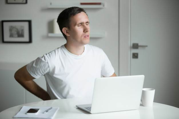 Young Man With His Hands At His Back Stretching After Working At Laptop 1163 2360